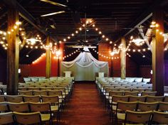 A wedding ceremony setup in the Loft. The warm wood tones are really accented by the strings of light.