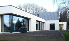 This project involved the extension of an existing house. The existing house was a dormer style cottage, located within a woodland context and bounding the shores of Lough Derg. The design concept was to transform the existing cottage while retainin Modern Bungalow Exterior, Bungalow House Design, Modern House Design, Bungalow Designs, Bungalow Extensions, House Extensions, House Designs Ireland, Flat Roof House, Woodland House