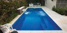 Rectangular swimming pool with square corners that provides you with a modern and elegant design. There is a bench running the length of the pool Above Ground Swimming Pools, Swimming Pools Backyard, Swimming Pool Designs, In Ground Pools, Pool Landscaping, Pools Inground, Fiberglass Pool Cost, Fiberglass Swimming Pools, Kleiner Pool Design