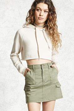 A mini skirt featuring a zipper fly and button closure, two front slip pockets, double cargo flap pockets, and back welt pockets.