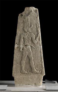 Stèle du dieu à la plume  XVIe - XIVe siècle avant J.-C.  Ras Shamra-Ougarit, acropole Calcaire  Fouilles C. Schaeffer, 1930 Département des Antiquités orientales AO 13174