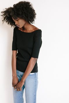 Achro Off The Shoulder Knit Top in black features a slim fit in a mid-weight, textured hand feel. Model is 5'9