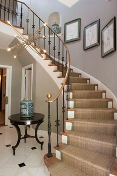 Designed by Matthew Moore, this winding staircase with a gold banister features floral sketches and pottery on the adjoining wall. The gold motif is echoed in the starlike modern chandelier hovering in the foyer. Staircase Runner, Winding Staircase, Curved Staircase, Staircase Design, Staircase Landing, Stair Runners, Transitional Living Rooms, Transitional House, Transitional Lighting