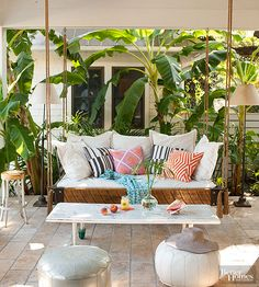A hanging daybed is a fresh twist on the standard porch swing, while plenty of pillows layer in comfort. Poufs are easy to maneuver and move around the porch for different seating configurations. Secret to Pretty: Consider the surroundings and embrace nature. What's around a porch is as important as what's on it, so give a little love to the plantings and landscape around your porch. Here, palm and banana trees wrap the porch in a jungle-like embrace./