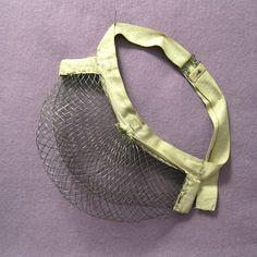 """Victorian Wire mesh bustle. The fashion for this wire mesh bustle came in the 1880s when the long skirt was pulled to the back and draped on top of this bustle. Adjustable one inch wide twill tape wraps around all but the largest waists with the 10-1/2"""" wide x 5"""" deep pre-formed wire mesh across the back stapled to the tape. By this time, fashion dictated that dresses would have a more slender silhouette, with the lady becoming more emancipated, hence not as many underpinnings were required."""