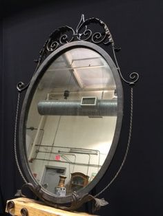OVAL SHAPED MIRROR IN WROUGHT IRON FRAME, MEASURES 21 IN. W X 30 IN. H.