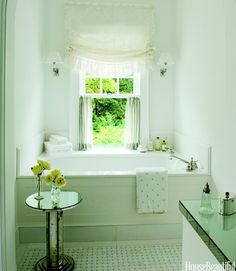 In a Virginia home's master bathroom, designed by William Hodgins, the greatest luxury of all: a tub with a garden view. Adding sparkle are an antique mirrored table and white basket-weave floor tile from Waterworks. Frédéric Vasseur  - HouseBeautiful.com