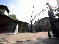 """Pope Francis walks through the notorious gate at Auschwitz with the sign """"Arbeit Macht Frei"""" (Work sets you free) during his visit to the former Nazi death camp in Poland."""