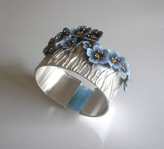 Bracelet in an oval shape (perfectly adapts to the wrist) made of silver 930 and natural leather. Hand-painted flowers of forget-waterproof and abrasion resistant paint decorated decorative veins. The whole finished blue organza. Silver frosted. Bracelet photographed on a very thin wrist (14.5 cm), on the wrist of a wider circumference would be more fitting.