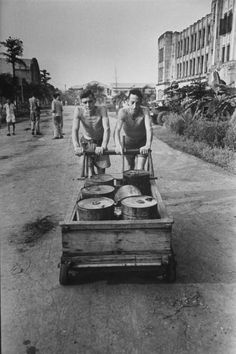 Pair of emaciated Americans, former POWs of the Japanese, push cart filled with edible oils to be used to feed other freed prisoners formerly held in University of Santo Tomas by the Japanese, following the liberation of the prison by Allied forces. Date taken: February 5, 1945. Photographer: Carl Mydans. Credit: Life Magazine. University Of Santo Tomas, Edible Oil, Cool Photos, Interesting Photos, Life Magazine, Manila, Prison, Wwii, Philippines