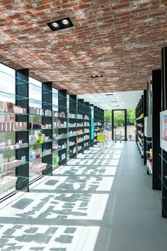 Pharmacy in Berendrecht (Belgium) by sculp[IT]architects | brick ceiling and steel colums which are also the windowprofiles ànd supporting for the glass shelves | photograpy www.roymans.com