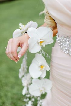 Gorgeous orchid bracelet: http://www.stylemepretty.com/2015/03/31/elegant-outdoor-wedding/ | Photography: Caroline Lima Photography - carolinelima.com