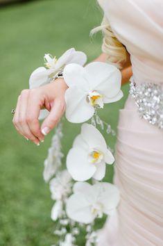 Gorgeous orchid bracelet: http://www.stylemepretty.com/2015/03/31/elegant-outdoor-wedding/ | Photography: Caroline Lima Photography - carolinelima.com