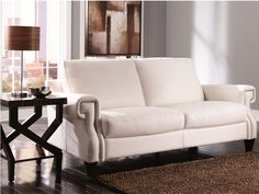 Complete your modern-chic look with some luxurious white leather and nailhead studded accents! || Zola Sofa cort.com