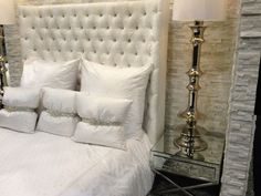 Rhinestone buttons, white bedding, mirrored tables, and stone wall.