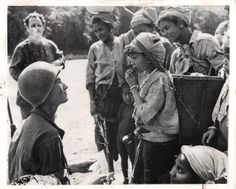 1944- One of Merrill's Marauders, Pvt. Wayne Martin, during a rest period of the outfit's march in Burma, shows a native child how to enjoy a stick of chewing gum.