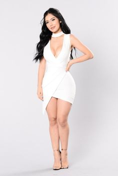 - Available In White and Black - Sleeveless Mini Dress - Asymmetrical Bottom - High Neck - Back Zipper Closure - Made in USA - 97% Polyester 3% Spandex