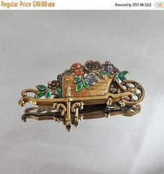 This #vintage flower wagon brooch is so beautiful!  It features red, purple, green and pink flowers enamel flowers in a garden wheelbarrow or wagon in gold tone.  Very detai... #ecochic #etsy #jewelry #jewellery