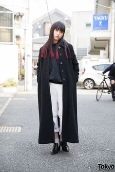 This is Ayaca, a 19-year-old model and student. She has dark hair with bangs and pink tips. Ayaca is wearing a resale sweatshirt, black coat, cuffed white pants, heeled loafers from OZOC, and earrings from Disney. She has silver and black nails and lace socks. She likes to shop from Kujaku and Clique Tokyo, and she's a fan of rock and punk music, especially [Alexandros].