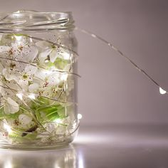 Fill a mason jar with fresh flowers and battery operated fairy lights to create magical #Wedding centerpieces!