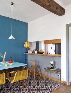 Le trio parfait (du jaune, du bleu et du vert) avec du bois et un carrelage à motifs : à la fois moderne et authentique. Détail pointu : le liseré rouge qui encadre le mur bleu.