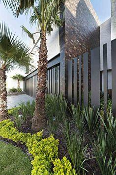 jardin avec palmiers et plantes vertes et un brise-vue élégant en bois