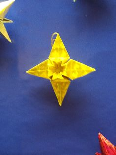 this star folded from a square features a raised 3D cross with a sink fold in the center