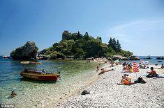 Italian charm: Sunbathers relax on Isola Bella beach in Taormina, Sicily, Italy