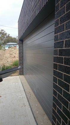 Basalt garage, blue steel flash brick concrete driveway Brick Facade, Facade House, House Facades, Modern Exterior, Exterior Colors, Steel Sheds, Grey Brick, Concrete Driveways, Brick Colors