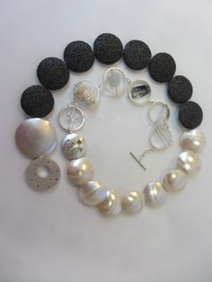 By Lona Northener. Black lava beads, Mother of by pbeads and silver circles with inclusions of keshi pearls, tourmalinated quartz and moonstone. silver hollow form toggle.