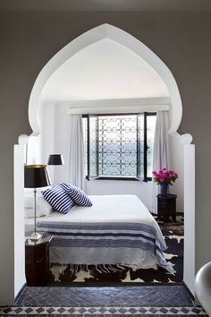 Love the Moroccan-inspired cutout doorway into this cozy blue and white bedroom.