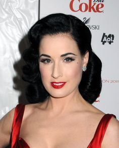 Reminiscent of 1940's hairstyles, Dita likes to wear her black locks in soft waves with the ends curled  under just like glamor women of the past did.    A deep side part makes a perfect starting point for a big swoop of style with the bangs being pushed up and back. This is a lovely 'do for those who love a touch of vintage and have shoulder length strands.  More on Dita Von Teese Vintage Hair