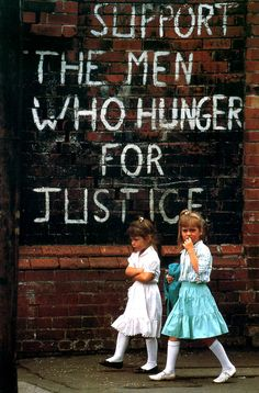 David Turnley: Two Catholic girls walk by a slogan supporting the hunger strikers of the Irish Republican Army and Sinn Fein. Belfast, Northern Ireland, 1988