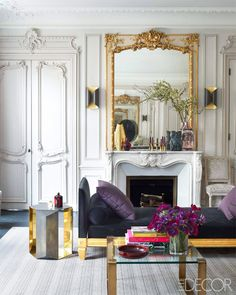 Velvet daybed in living space with purple pillows beside a marble fireplace with a leaning gold mirror on the mantle