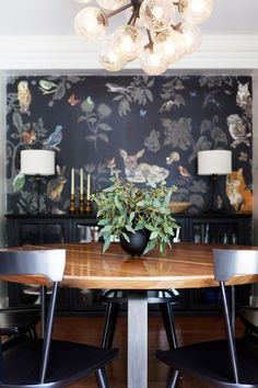 black wall paper and chairs, wood table, seeded eucalyptus centerpiece.