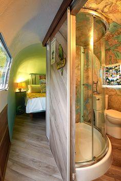 庭のウッドデッキの脇に置かれたロングボディのキャンピングトレーラーAIRSTREAMのバスルームとベッドルーム