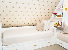 Incredible attic kids' room features sloped wall clad in Coronata Star Wallpaper over built-in daybed with storage drawers adorned with brass hardware beside a built-in reading nook with storage drawers below topped with taupe geometric pillows and built-in bookcase illuminated by Architectural Wall Sconce filled with toys and books atop herringbone carpeting.