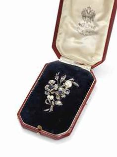 A JEWELLED GOLD AND SILVER-MOUNTED BROOCH BY FABERGÉ, PROBABLY MOSCOW, CIRCA 1910. In the form of a ribbon-tied bouquet of flowers, set with silver-mounted rose-cut diamonds, sapphires and pearls, the reverse with hinged gold pin; in the presentation silk and velvet-lined leather case, stamped 'Fabergé St Petersburg Moscow London' beneath the Imperial Warrant, applied with a silver plaque engraved with signatures of a group of prominent chemists and public figures of early 20th century St…