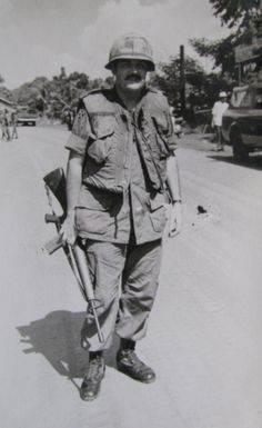 Maj. Norm Mac Lellan of Venice stands with his M-16 rifle in the middle of Highway One leading north out of Saigon after a firefight with t...