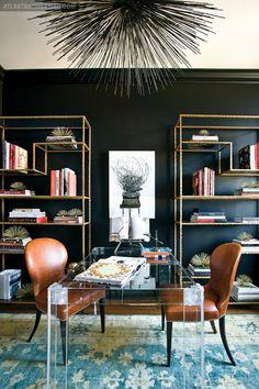 Chic - black walls, blue rug, lucite desk, great chandelier + gold bookshelves!