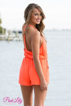 You will be dreaming of summer when you lay eyes on this romper! Neon coral romper with braided straps, pockets on each side, a button clasp to make a higher v-neck, and a tie around the waist.