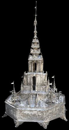 The monumental silver model of a Temple Burma dated 1914, was modelled at Mandalay Palace. The model is of repoussed and chased silver. At 84 centimeters or 33 inches tall, it is an exceptionally tall example of colonial Burmese silverwork. It stands on an eight-sided base that has eight elegant, open-work feet. There are scenes of log carting by elephants, log processing, as well as the Company's Rangoon head office.