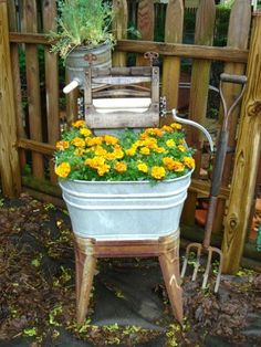 Part of a recycled washing machine and wash tub are now host to a mini-garden of yellow flowers.