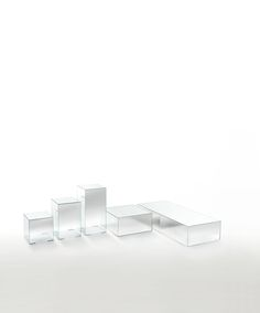 ILLUSION design Jean-Marie Massaud | Series of parallelepiped shaped low tables with mirroring top and degrading shading mirroring sides. Realized in 6 extralight glass, glued 45°.