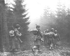 US troops of the 325th Glider Infantry Regiment, move through a fog to a new position in the Ardennes, december 1944.