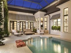 Striped awning by the pool at night.  1189 4th St South | Aqualane Shores in Naples, Florida
