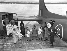 """The wartime mail from Canada was taking too long, so in late 1943, the government created the 168 Squadron RCAF, known as the """"Mailcan Squadron."""" During its thirty months in existence, pilots made 636 transatlantic flights in Liberators and B-17 Fortresses loaded with mail. This photo shows airmen loading mailbags into the fuselage of a 168 Heavy Transport Squadron """"Fort."""" (Photo Credit: Department of National Defence). For more: www.elinorflorence.com/blog/ww2-mail."""