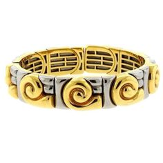 "An 18k yellow and white gold bracelet by Bulgari. The bracelet will fit up to a 6 1/4"" wrist and is 11mm wide. The weight of the piece is 58.5 grams. Marked: Bvlgari, Maker's mark. DESIGNER: Bulgari M"