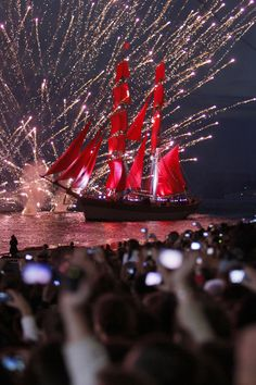 People observe a frigate with scarlet sails floating on the Neva River in St.Petersburg, Russia.The frigate participated in festivities marks school graduations which take place across the country.