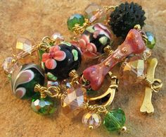 Rose Garden Dog Bone Bracelet Green Pink Gold with artisan lampwork beads, bling crystals, and gold dog collar and bone toggle clasp.  Handmade by For Love of a Dog Jewelry & Gifts